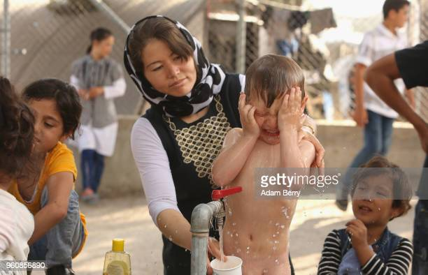 An Afghan woman gives her child a bath at the Moria refugee camp on May 20 2018 in Mytilene Greece Despite being built to hold only 2500 people the...
