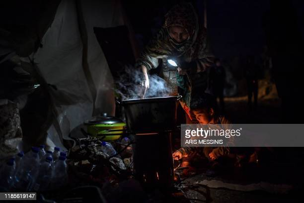 An Afghan woman holds a lamp as she cooks dinner with her son outside a tent at a makeshift camp next to the camp of Moria on the Greek island of...