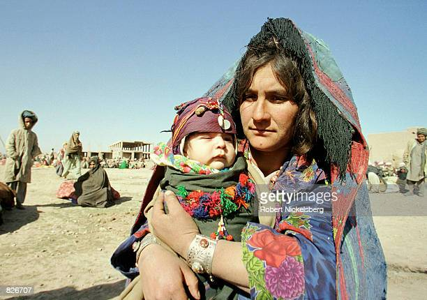 An Afghan woman holds her baby after their arrival at the Minarets refugee camp January 24 2001 in Herat Afghanistan The Afghans are fleeing the...