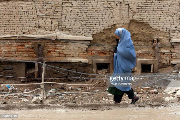 An Afghan woman in a burqa walks along a muddy street February 10, 2009 in Kabul, Afghanistan. Many side roads in the capitol city still remain...