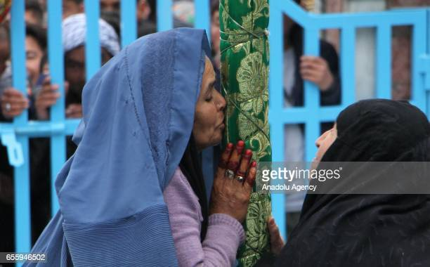 An Afghan woman kisses a religious flag as she celebrates the Persian New Year Nowruz at the Shrine of Saint Sakhi Saib in Kabul Afghanistan on March...