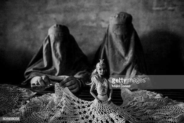 An Afghan woman learns how to knit a dress for a doll at a workshop sponsored by an American NGO called Mercy Group that seeks to help local females...
