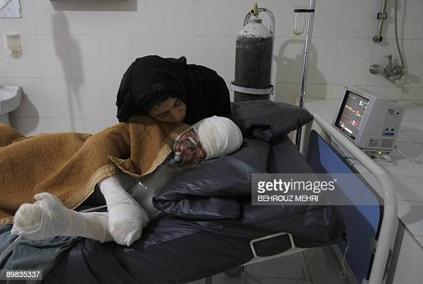 An Afghan woman listens to her daughter Ghodsi who committed selfimmolation and has been hospitalized since last week with 85% of her body covered in...
