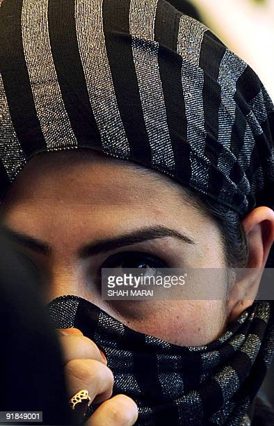 An Afghan woman listens to presidential candidate Abdullah Abdullah speak at a gathering in Kabul on September 27 2009 Afghanistan's main challenger...