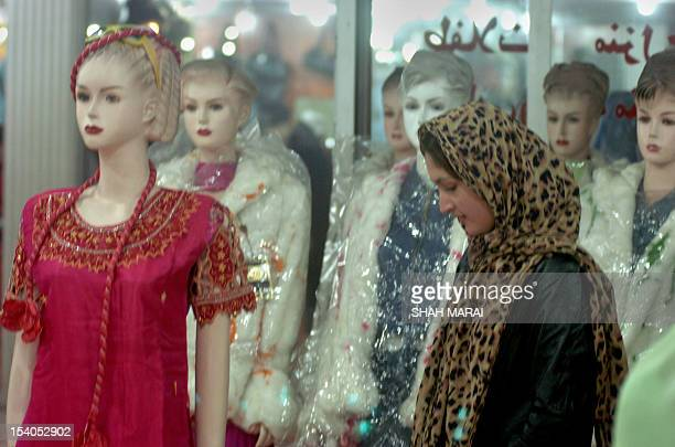 An Afghan woman looks along a line of mannequins displaying Western and Indian outfits at a shop in Kabul 29 December 2005 Women who were barred from...
