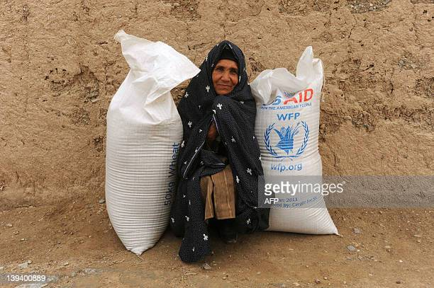 An Afghan woman looks on after receiving bags of wheat during a food donation at a World Food Program emergency appeal in Isahaq Sulaiman village of...