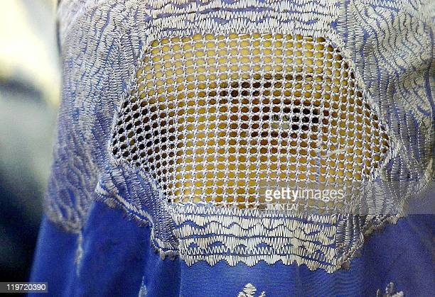 An Afghan woman looks out from beneath her burka in Kabul 14 January 2002 Millions of Afghan women were forced by the fundamentalist Taliban regime...