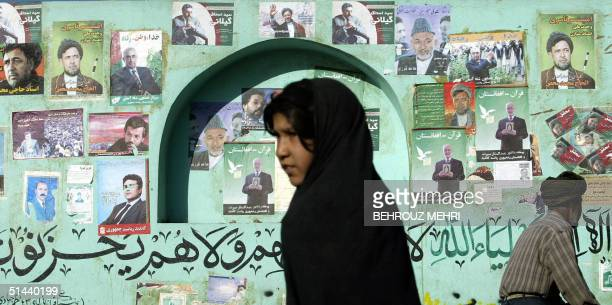 An Afghan woman passes by electoral posters of presidential candidates in Herat 600 kilometers west of Kabul 08 October 2004 Afghanistan is set to...