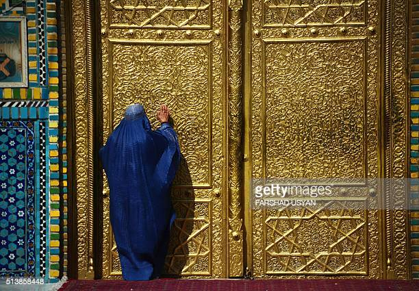An Afghan woman prays in a doorway of the courtyard of the HazrateAli shrine or Blue Mosque in MazariSharif on March 5 2016 / AFP / FARSHAD USYAN