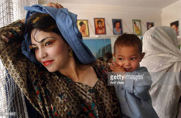 An Afghan woman puts on her burka after getting her hair and face made up for a wedding August 30, 2002 in Kabul, Afghanistan. On Fridays, beauty...