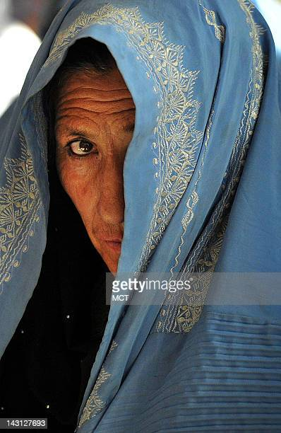 An Afghan woman shields her face while watching the International Women's Day celebration in the Governor's compound in Ghazni City Afghanistan March...