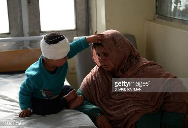 An Afghan woman sits next to a wounded child after receiving treatment at Indira Gandhi Children's Hospital after a powerful truck bomb attack in...