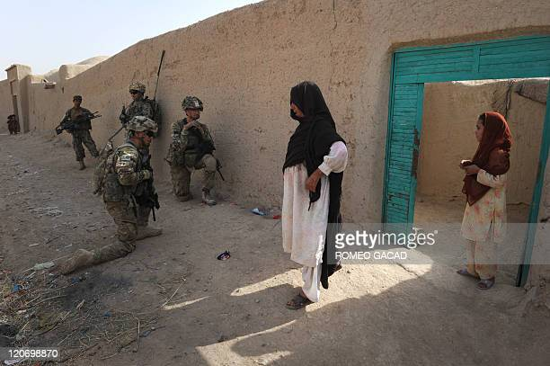 An Afghan woman stands in front of their gate as Afghan National Army soldiers check the house while US troops from the Charlie Company 287 Infantry...