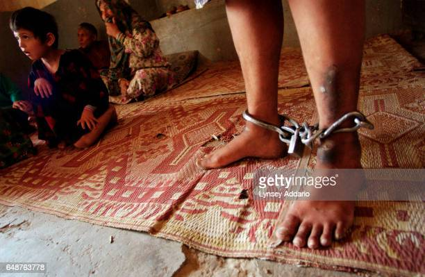 An Afghan woman stands with her ankles chained inside the women's ward of Kabul's only psychiatric hospital in Kabul Afghanistan on July 23 2002 She...
