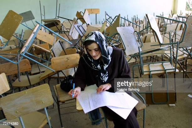 An Afghan woman takes a university entrance exam February 20 2002 in a classroom destroyed during Afghanistans civil war at Kabuls Polytechnic...