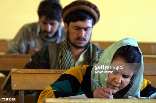 An Afghan woman takes a university entrance exam February 20 2002 with male classmates at Kabuls Polytechnic Institute An estimated 8000 students...