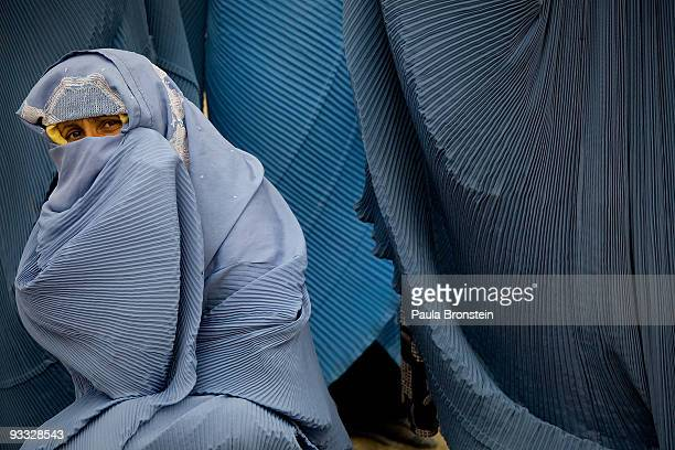 An Afghan woman tries to keep warm while waiting in line at a CARE food distribution aimed at widows November 23 2009 in Kabul Afghanistan The CARE...