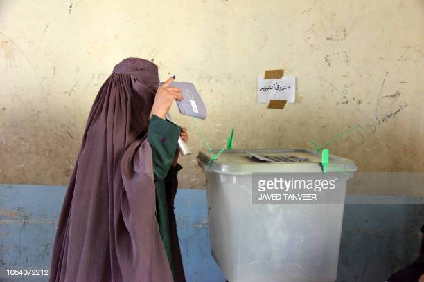 TOPSHOT An Afghan woman voter casts her ballot at a polling centre for the country's legislative election in Kandahar province on October 272018...