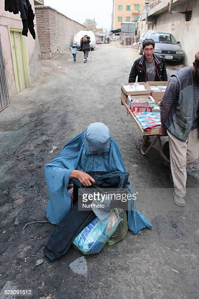 An Afghan woman Waits to give her clothes to drying clothes at a shop in Kabul Afghanistan on October 202014