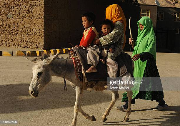 An Afghan woman walks beside a donkey carrying her children along a street in Bamiyan on July 6 2008 The cavemonasteries of Bamiyan and the niche...