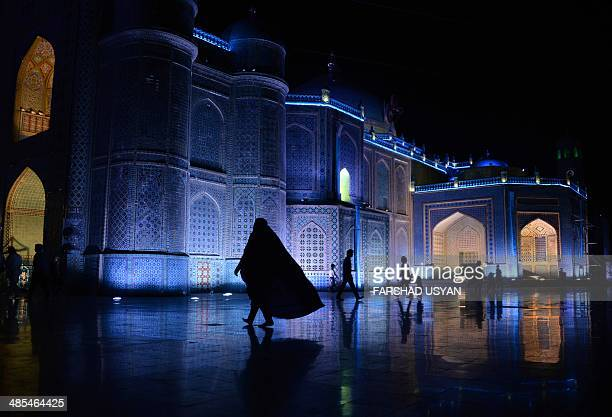 An Afghan woman walks in the courtyard of Hazrate Ali shrine or 'Blue Mosque' in the northern city of Mazare Sharif on April 17 2014 The mosque whose...