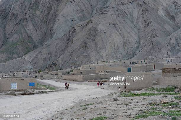 An Afghan woman walks with her cow in Qara Zaghan village in Baghlan province on May 7 2013 Afghanistan is one of the world's poorest countries where...