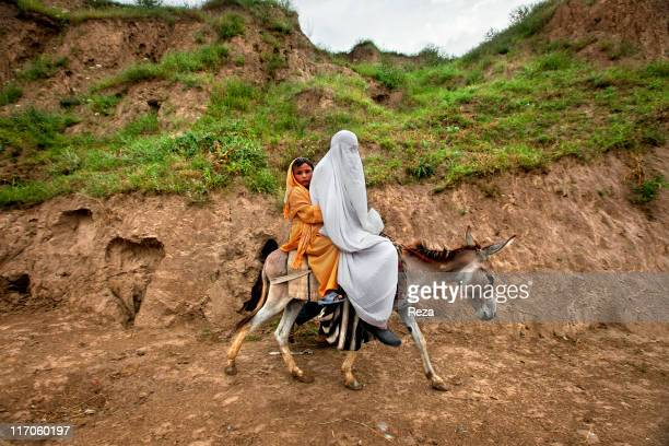 An Afghan woman wearing a burqa and her daughter riding a donkey on the road linking Khvajeh Baha Od Din and Dashte Qal'eh May 19 2009 in Takhar...