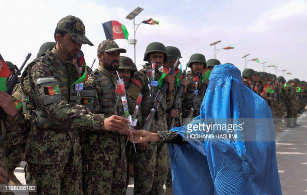 An Afghan woman wearing a burqa gives roses to Afghan National Army soldiers during a ceremony in a military base in the Guzara district of Herat...