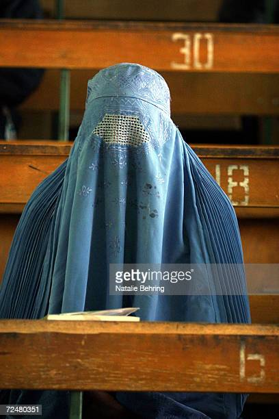 An Afghan woman wearing a burqa sits in a lecture hall February 20 2002 as she waits to take a university entrance exam at Kabuls Polytechnic...
