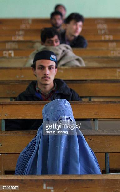 An Afghan woman wearing a burqa sits in a lecture hall with male classmates February 20 2002 as they wait to take a university entrance exam at...