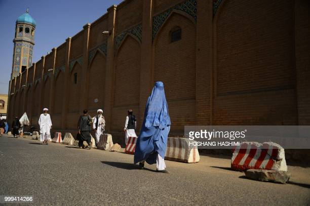 TOPSHOT An Afghan woman wearing a burqa walks in front of Jama Mosque in Herat on July 15 2018