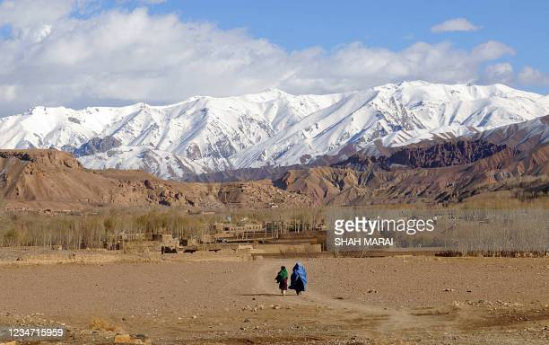 An Afghan woman with daughter walk in the old city of Bamiyan on November 9, 2009. Bamiyan, some 200 kilometres northwest of Kabul, stands in a deep...