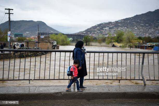 An Afghan woman with her child cross a bridge after heavy rain falls along the Kabul river in Kabul on April 16 2019 Torrential rainstorms have...