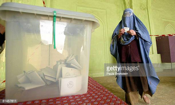 An Afghan women walks to the ballot box to cast her vote as in Afghanistan's first democratic election at a polling station October 9 2004 in Kabul...