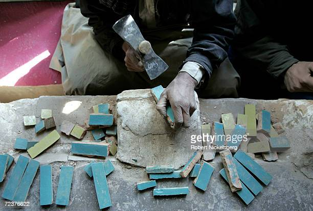 An Afghan worker chips away excess clay on glazed tiles inside the 12th century Blue Mosque on February 17 2005 in Herat Afghanistan Herat's Blue...