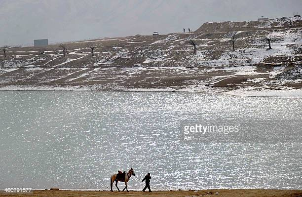 An Afghan youth selling horse rides waits for customers at the Qargha Lake on the outskirts of Kabul on January 3 2014 The park in the Afghan capital...