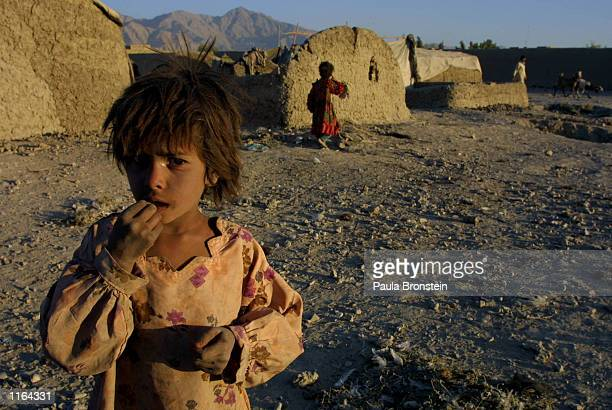 An Afghani refugee girl living at the Pung Puti refugee camp on the outskirts of Quetta Pakistan stands in a common area September 29 2001 The...