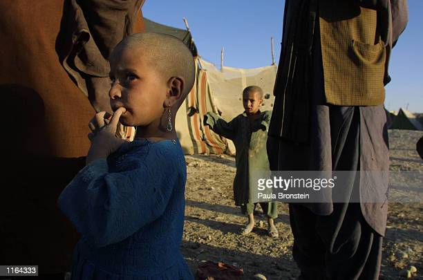 An Afghani refugee girl living at the Pung Puti refugee camp on the outskirts of Quetta Pakistan chews her finger September 29 2001 The refugees who...