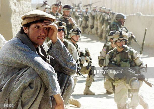 An Afghani squats on a wall while a group of US Army soldiers from the 82nd Airborne Division secure an area during the inspection of a local bazaar...