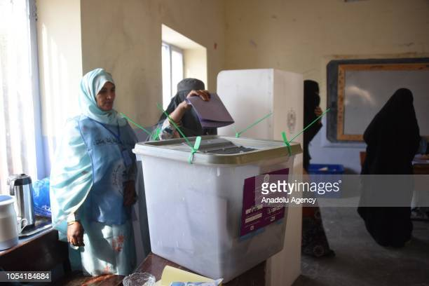 An Afghani voter casts her ballot for the parliamentary elections one week later than the rest of the country delayed due to a highprofile...