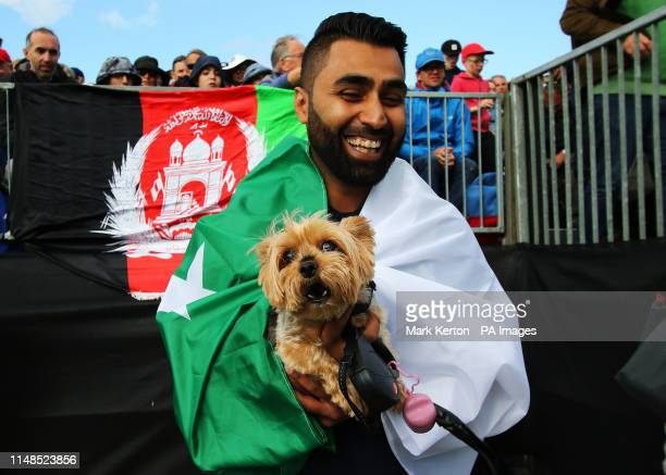 An Afghanistan fan and his dog watch on during the ICC Cricket World Cup group stage match at the County Ground Taunton