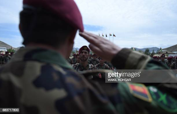 An Afghanistan National Army soldier salutes during a graduation ceremony at a commando unit base in Reesh Khor on the outskirts of Kabul on May 16...