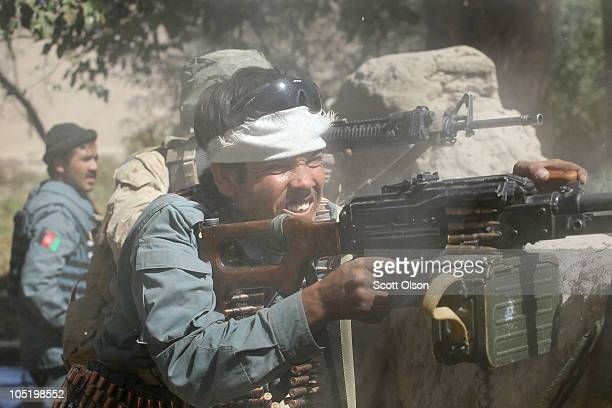 An Afghanistan National Police officer opens fire with a machine gun on a Taliban position during a firefight alongside US Marines with the Police...