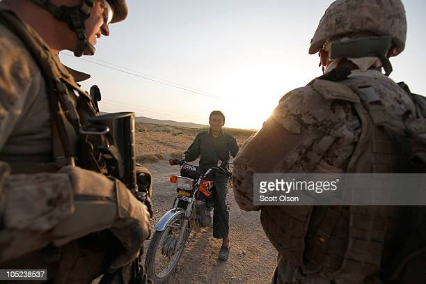 An Afghanistan National Policemen reports to US Marines 1st Lt Ryan Cooper of Lancaster PA and an Afghan interpreter working with the Police Advisory...