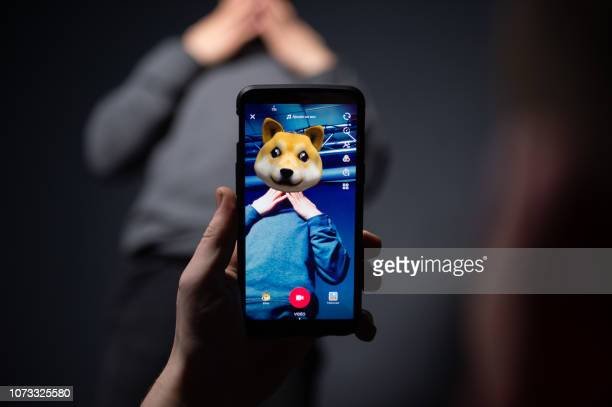 An AFP collaborator poses for a picture using the smart phone application TikTok on December 14 2018 in Paris TikTok is a Chinese shortform...
