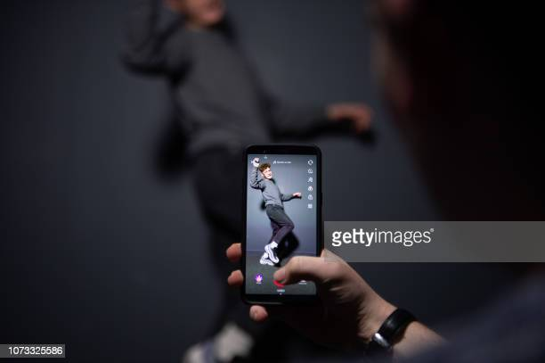An AFP collaborator poses for a picture using the smart phone application TikTok on December 14, 2018 in Paris. - TikTok, is a Chinese short-form...