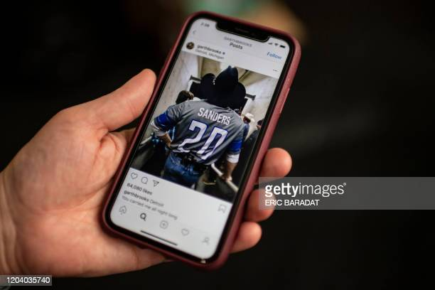 """An AFP journalist holds a smartphone displaying the Instagram account of Country Music star Garth Brooks showing him wearing a """"Sanders 20"""" jersey on..."""