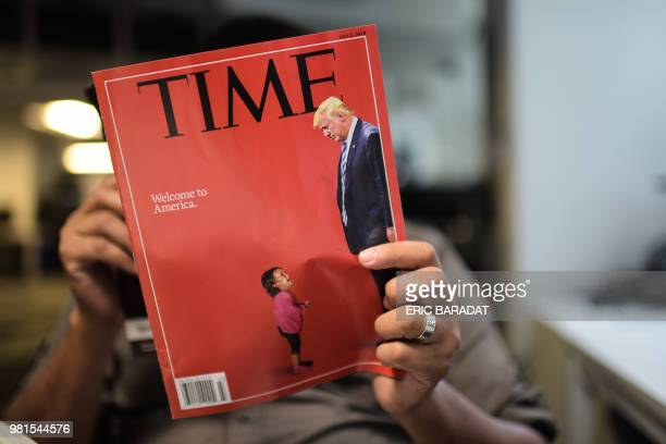 An AFP journalists reads a copy of Time Magazine with a front cover using a combination of pictures showing a crying child taken at the US Border...