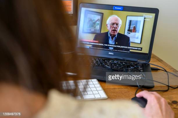 An AFP political correspondent working from home watches a video from the Bernie Sanders presidential campaign as Sanders announces the suspension of...