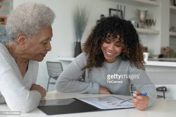 an african american adviser meets with a senior client stock photo - medical insurance stock pictures, royalty-free photos & images